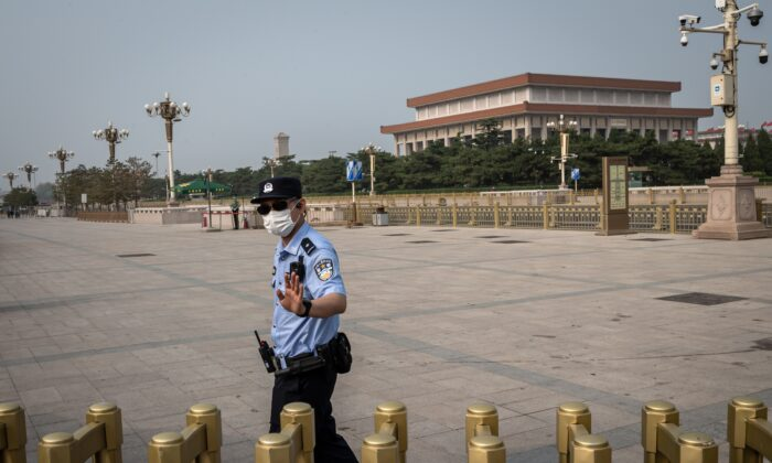 A police officer gestures as he secures an area outside Beijing's Tiananmen Square (back) on World Press Freedom Day in Beijing, China on May 3, 2020. (NICOLAS ASFOURI/AFP via Getty Images)