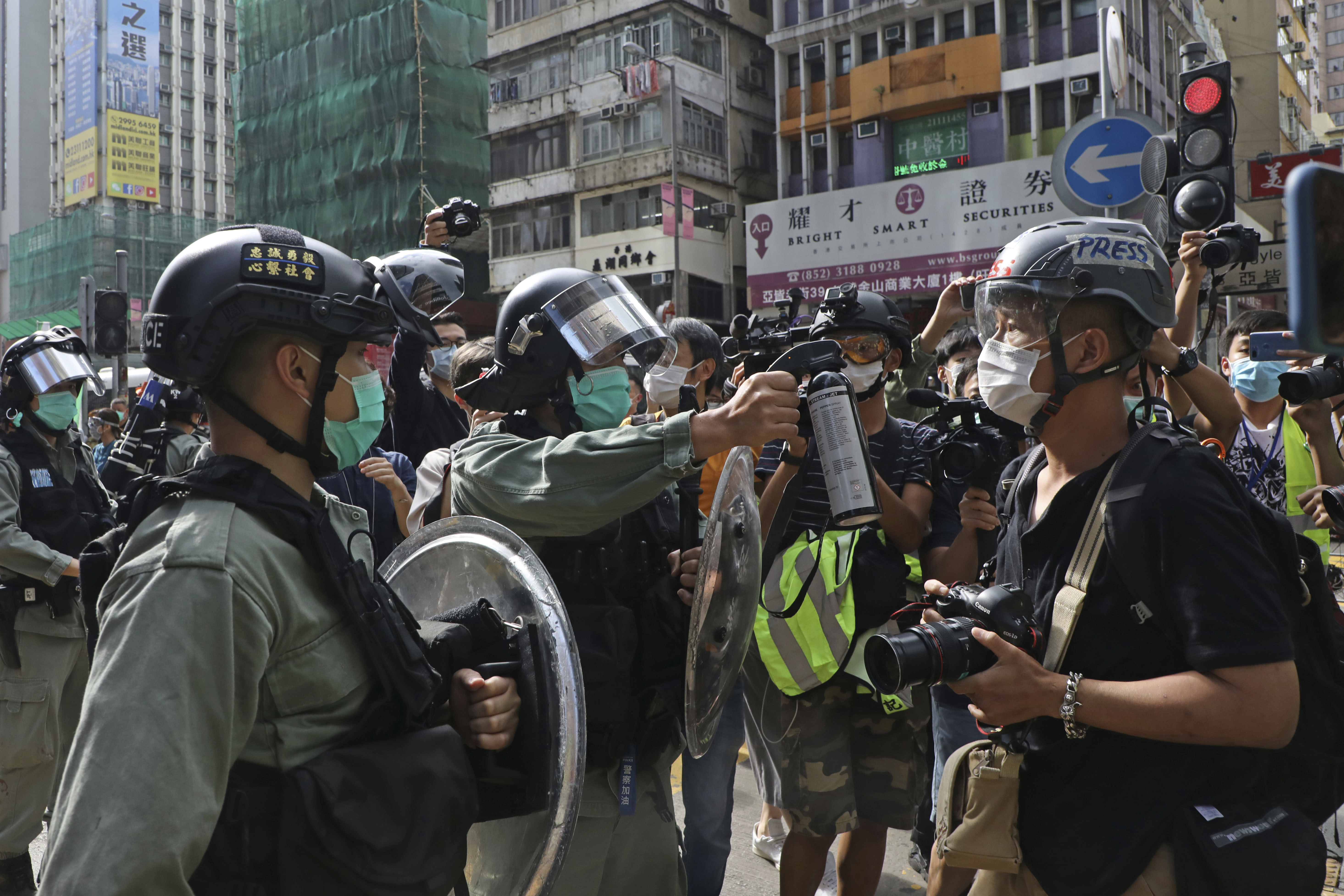 A riot police points the pepper spray to journalists