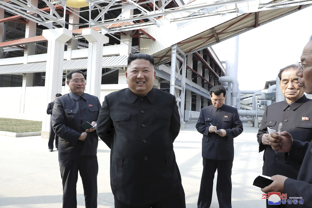 Kim Jong Un (C) visits a fertilizer factory