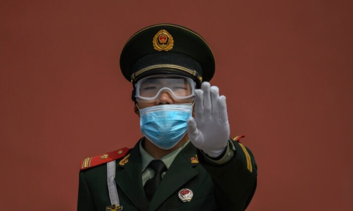 A Chinese paramilitary police officer gestures as he wears a protective mask while standing guard at the entrance to the Forbidden City as it re-opened to limited visitors in Beijing, China, on May 1, 2020. (Kevin Frayer/Getty Images