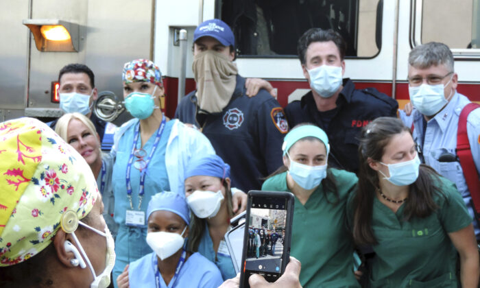 A medical worker at NYU Langone Medical Center is asked to take a group photo of her medical staff colleagues and New York City firefighters who showed up to the hospital for the nightly 7 p.m. clapping appreciation given to health care workers in the city on May 2, 2020. (Sally Stapleton/AP Photo)