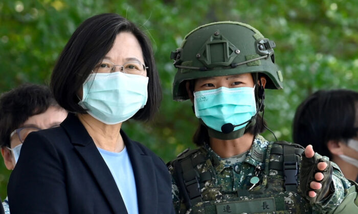 Taiwan President Tsai Ing-wen (L) listens to a masked soldier amid the coronavirus pandemic during her visit to a military base in Tainan, southern Taiwan, on April 9, 2020. (Sam Yeh/AFP via Getty Images)