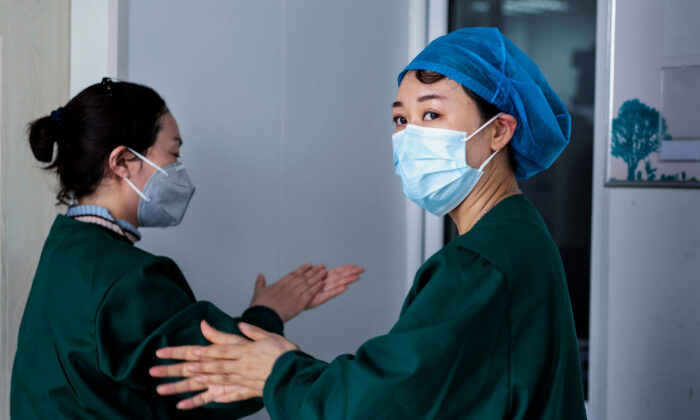 Medical personnel are working on nucleic acid testing as part of CCP virus pandemic measures, at a health services centre in Suifenhe in China's northeastern Heilongjiang province on April 24, 2020. (STR/AFP via Getty Images)