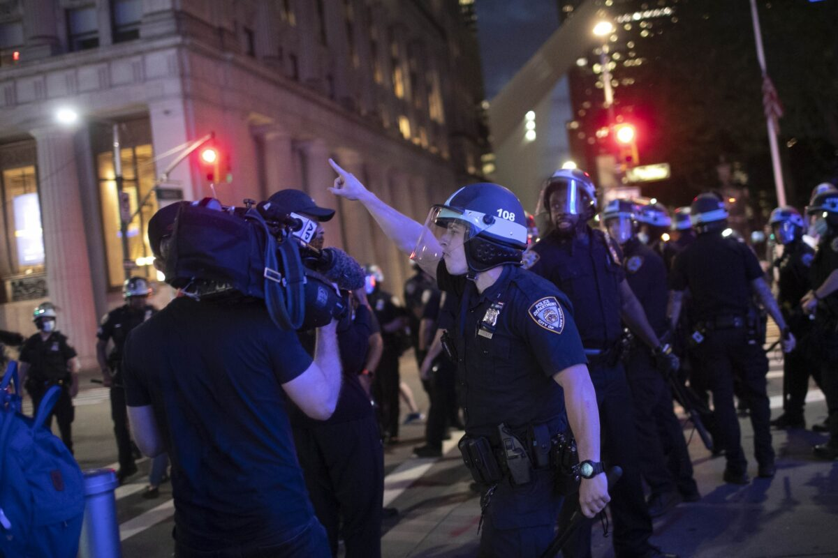 A police officer shouts at Associated Press videojournalist Robert Bumsted