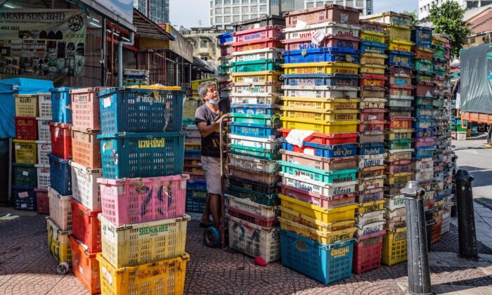 As Malaysia eases its lockdown measures related to the CCP virus, a worker wearing a mask arranges empty crates at a fruit market in Kuala Lumpur on May 4, 2020. (Mohd Rasfan/ AFP via Getty Images)