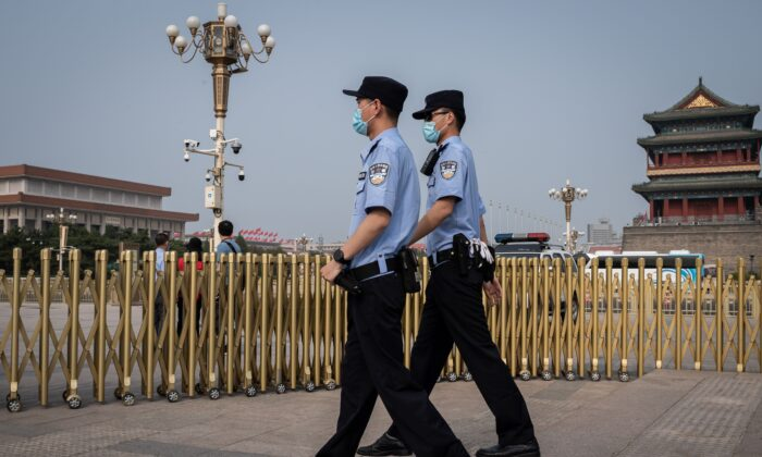 Police officers patrol an area outside Beijing's Tiananmen Square (back) on World Press Freedom Day on May 3, 2020. (Nicolas Asfouri/AFP via Getty Images)
