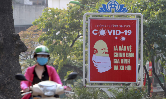A motorcyclist drives past a poster calling people to take care of their health against the new coronavirus in Hanoi, Vietnam on April 14, 2020. (Hau Dinh/AP)