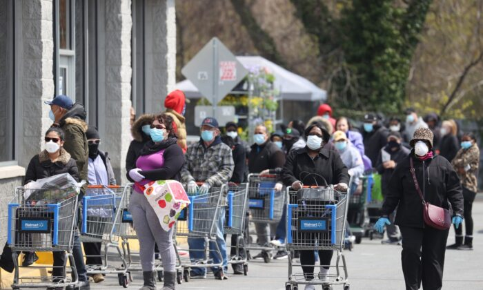 People wearing masks and gloves wait to enter a Walmart in Uniondale, N.Y., on April 17, 2020. (Al Bello/Getty Images)