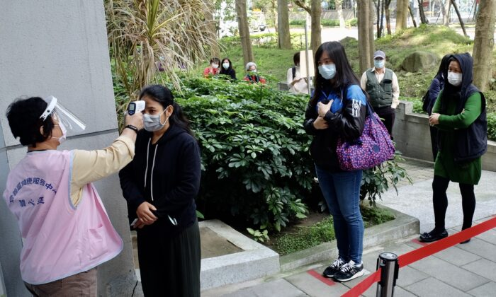A masked local resident (2nd L) has her temperature checked as people line up to buy face masks from vending machines at the Xinyi District Health Center in Taipei, Taiwan, on April 14, 2020. (Sam Yeh /AFP via Getty Images)