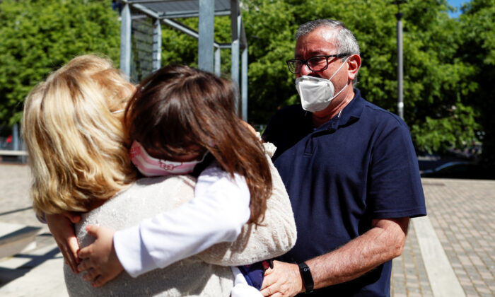 Domenico di Massa and Mariantonia Gangemi embrace their granddaughter Cecilia for the first time in two months after Italy allowed families to see each other again as the country begins a staged end to a nationwide lockdown due to a spread of the coronavirus disease (COVID-19), in Rome, Italy, May 4, 2020. (Yara Nardi/Reuters)