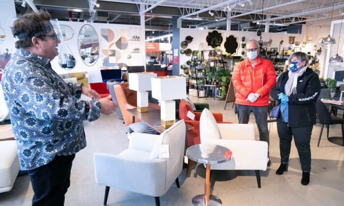 A sales clerk keeps his distance from clients at a furniture store in St-Jean-sur-Richelieu, Que. on May 4, 2020. (The Canadian Press/Paul Chiasson)