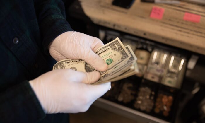 Worker seen counting money with protective gloves at Warehouse 4 Coffee Shop in Vandalia, Ohio, on March 15, 2020. (Brad Lee/AFP via Getty Images)