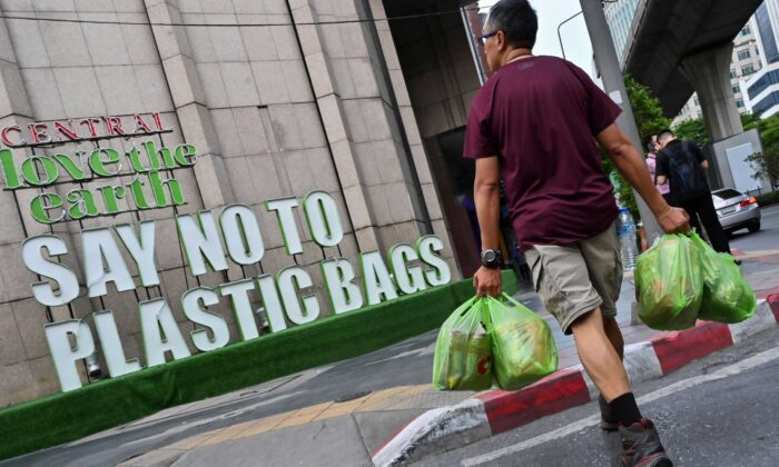 A man carrying goods in plastic bags crosses a street where a sign promoting a plastic bag-free shopping experience is displayed outside a department store in Bangkok on Aug. 13, 2019. (Romeo Gacad/AFP via Getty Images)