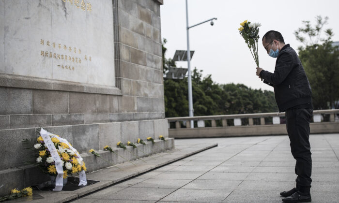 A resident presents flowers to martyrs who died in the fight against the CCP virus outbreak and compatriots who died of the disease in Wuhan, China on April 4,2020. (Getty Images)