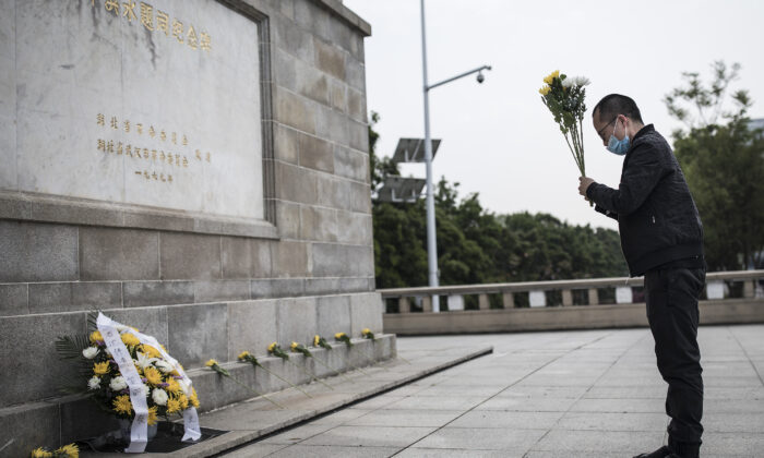 A resident presents flowers to martyrs who died in the fight against the CCP virus outbreak and compatriots who died of the disease in Wuhan, China on April 4, 2020. (Getty Images)