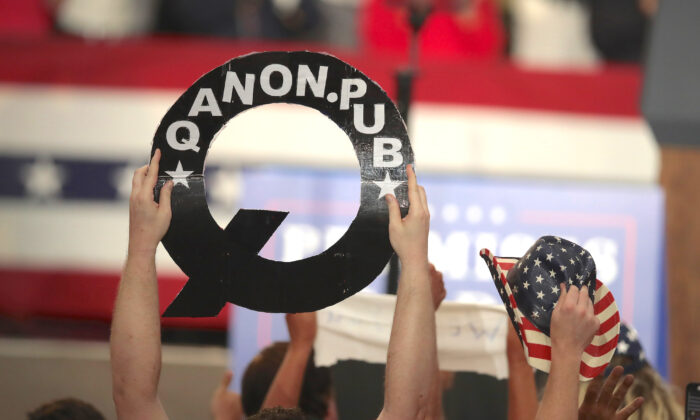 A rallygoer holds up a cutout of the letter Q, in Lewis Center, Ohio, on Aug. 4, 2018. (Scott Olson/Getty Images)