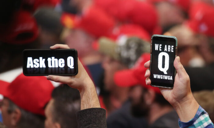 People hold up smartphones with QAnon-related messages on display, at a rally in Las Vegas, Nevada, on Feb. 21, 2020. (Mario Tama/Getty Images)