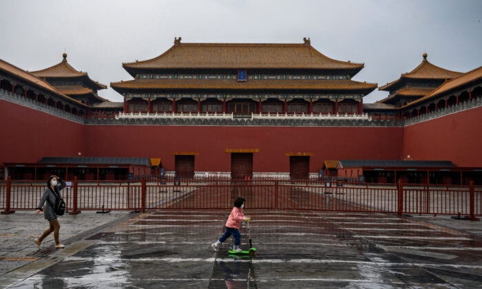 A Chinese girl wears a protective mask as she rides her scooter outside the gate of the Forbidden City, which remains closed to visitors, in Beijing, China, on April 19, 2020. (Kevin Frayer/Getty Images)