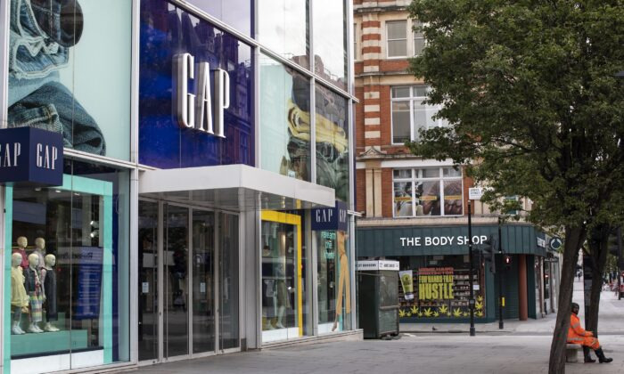 A man sits outside a closed Gap store in London, UK, on May 1, 2020. (Dan Kitwood/Getty Images)