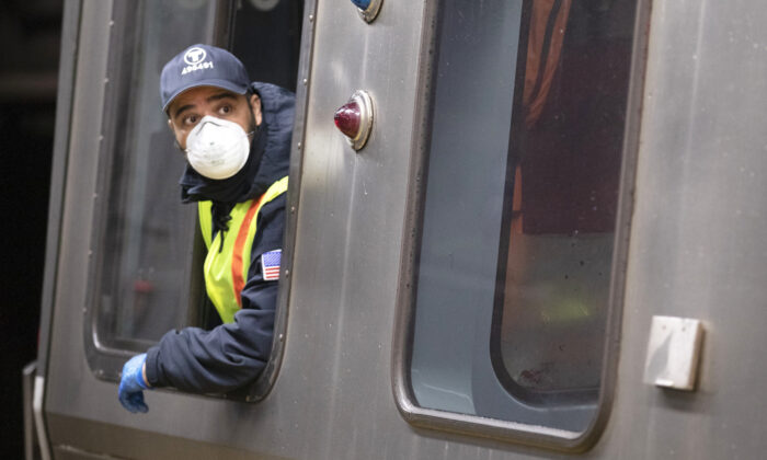Train driver wearing a protective mask operates the doors of a Massachusetts Bay Transportation Authority's Blue Line subway car at Maverick Station in Boston on April 24, 2020. (Michael Dwyer/AP)