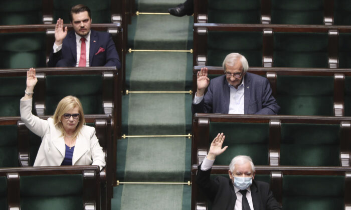 Poland's ruling party leader Jaroslaw Kaczynski, lower right, wearing an mask, and ruling party members vote in parliament to approve legislation for all-postal voting after Sunday presidential election was postponed due to organizational problems, in Warsaw, Poland, on Thurs., May 7, 2020. (Czarek Sokolowski/AP Photo/)
