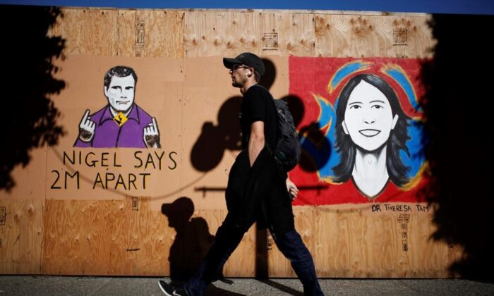 People walk by a mural of sign-language interpreter Nigel Howard and Chief Public Health Officer Dr. Theresa Tam created by artist Ian Morris seen along Government St. in Victoria, B.C., on May 6, 2020. (The Canadian Press/Chad Hipolito)