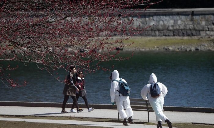 Two people wearing personal protective equipment, including respirators and coverall suits in-line skate on the seawall at Stanley Park in Vancouver on April 5, 2020. (Darryl Dyck/The Canadian Press)