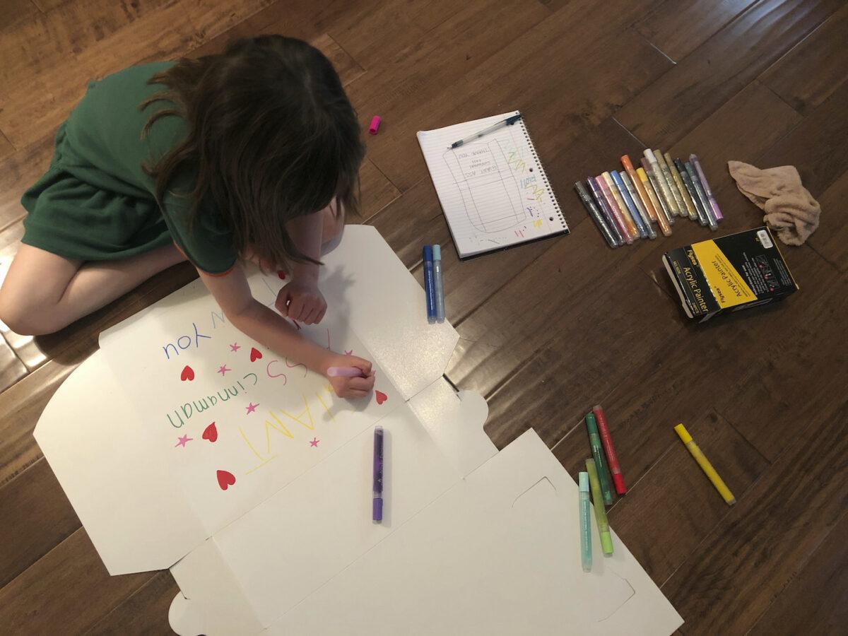 little girl decorates cinnamon roll box
