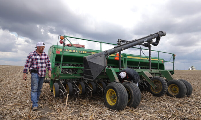 John Duffy (R) and his son Dan make a repair to a grain drill while planting soybeans near Dwight, Ill., on April 23, 2020. (Scott Olson/Getty Images)