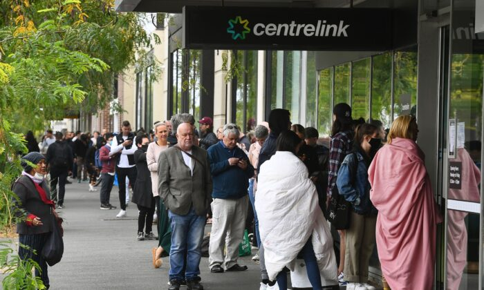 Hundreds of people queue outside an Australian government welfare centre, Centrelink, in Melbourne on March 23, 2020. (William West/AFP via Getty Images)