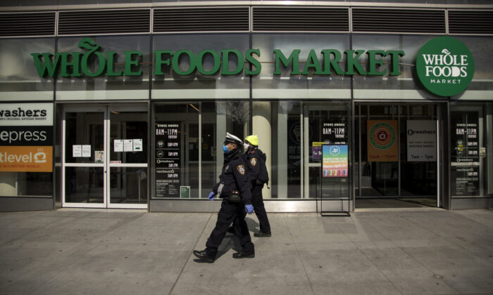 Two New York City Police Department Traffic Enforcement agents walk past the Whole Foods Market on April 14, 2020 in Brooklyn. (Justin Heiman/Getty Images)