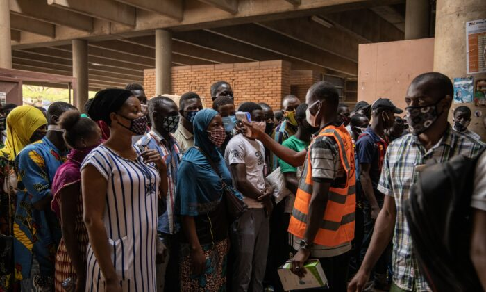 A communal agent measures the body temperature of traders at the opening of Rood Wokos great market in Ouagadougou, Burkina Faso, on April 20, 2020, after the market was closed since March 25, 2020, as a preventive measure against the spread of COVID-19. (Olympia de Maismont/AFP via Getty Images)