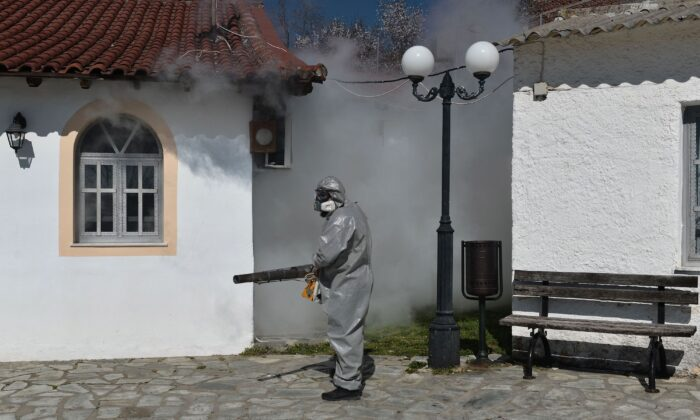 A worker uses a thermal fogger to disinfect outside of a church in Thessaloniki, Greece, on March 12, 2020. (Sakis Mitrolidis/AFP/Getty Images)