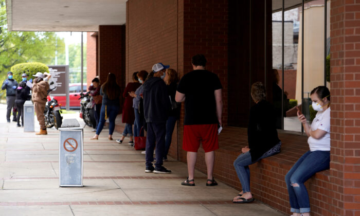 People who lost their jobs wait in line to file for unemployment at an Arkansas Workforce Center in Fayetteville, Ark., on April 6, 2020. (Nick Oxford/Reuters)