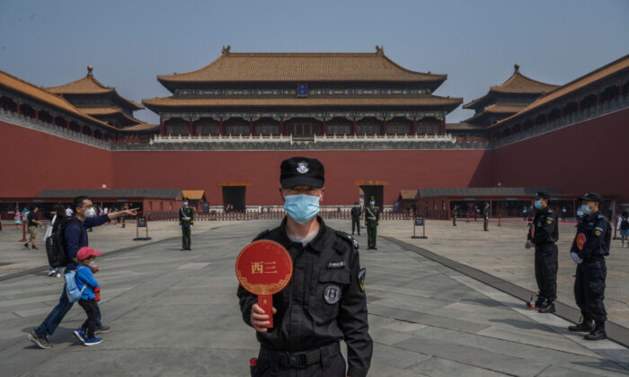 A Chinese guard wears a protective mask as he stands at the entrance to the Forbidden City as it re-opened to limited visitors or the May holiday, in Beijing, China, on May 1, 2020. (Kevin Frayer/Getty Images)