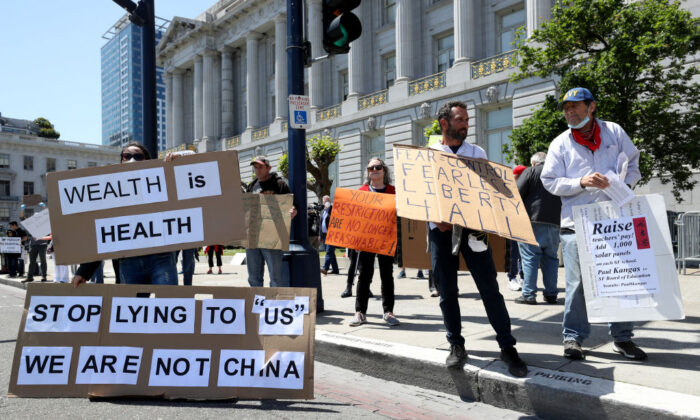 Demonstrators protest California Gov. Gavin Newsom's continued statewide shelter in place order outside of San Francisco City Hall in San Francisco, Calif., on May 1, 2020. (Justin Sullivan/Getty Images)