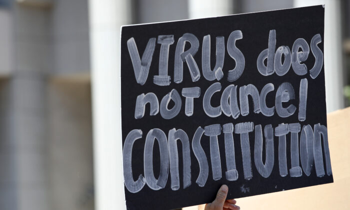 Activists hold signs and protest the California lockdown due to the coronavirus (Covid-19) pandemic, in San Diego, Calif., on May 1, 2020. The protesters demands included opening small businesses, churches as well as support for President Trump. (Sean M. Haffey/Getty Images)