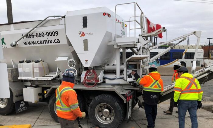 Workers get set to pour cement from a truck at the GO train station in Oakville, Ont., on Jan.28, 2020. (The Canadian Press/Richard Buchan)
