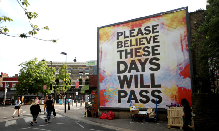 People walk past a large billboard reading 'Believe me, these days will pass' at London Fields on May 07, 2020 in London, England. (Alex Pantling/Getty Images)