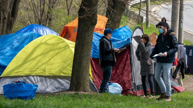 Outreach workers from The Salvation Army visit with residents of a roadside tent encampment n Toronto, on May 5, 2020. (Frank Gunn/The Canadian Press)
