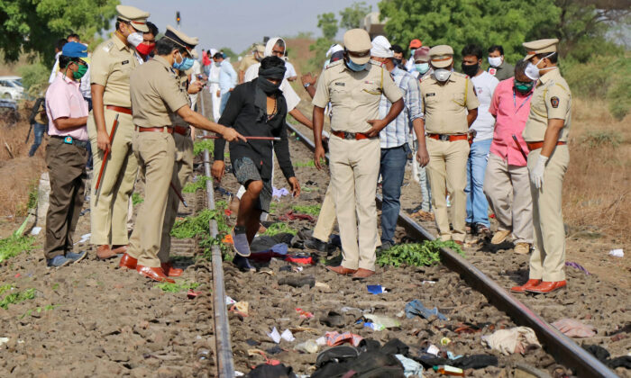 Police officers examine the railway track after a train ran over migrant workers sleeping on the track in Aurangabad district in the western state of Maharashtra, India, on May 8, 2020. (Stringer/Reuters)