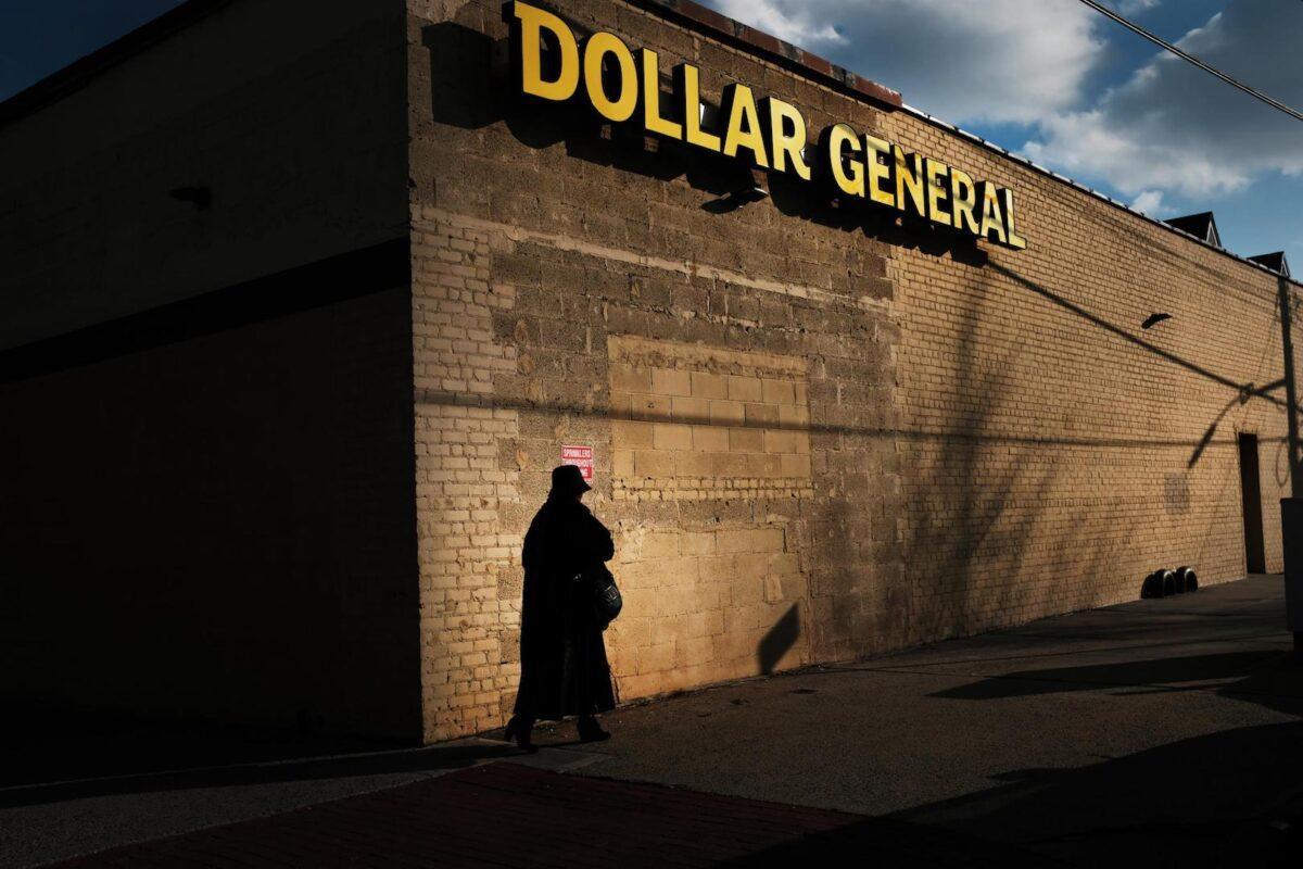 A woman walks by a Dollar General store o
