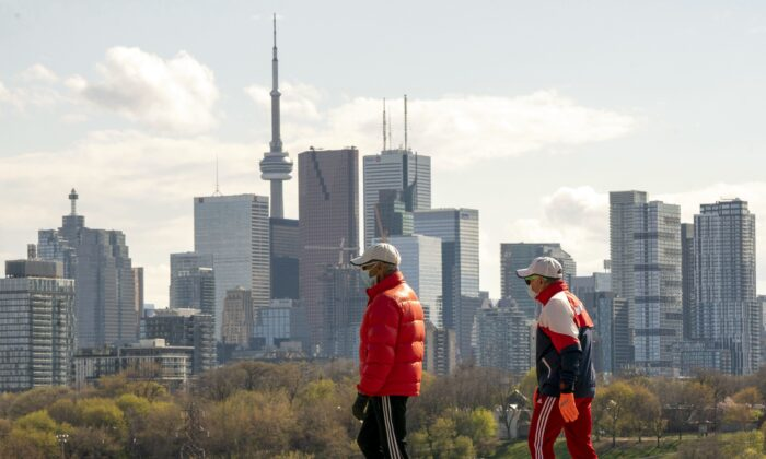 Men wearing masks to protect against COVID-19 take a walk in Toronto on May 7, 2020. (The Canadian Press/Frank Gunn)
