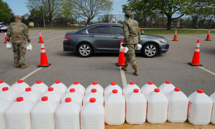 Members of the Massachusetts Army National Guard distribute free milk, offered instead of dairy farmers throwing away excess milk due to lower demand amid the COVID-19 outbreak, in Boston, Mass., on May 7, 2020.  (Brian Snyder/Reuters)