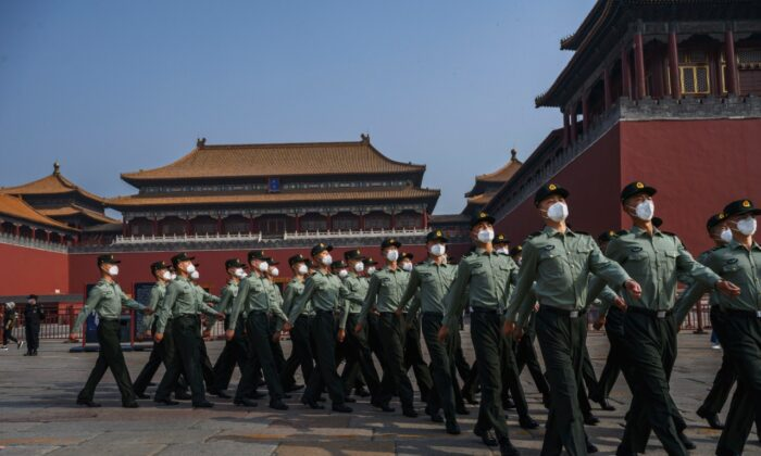 Chinese paramilitary police wear protective masks as they march by the entrance to the Forbidden City as it reopened to limited visitors for the May holiday, on May 2, 2020 in Beijing, China. (Kevin Frayer/Getty Images