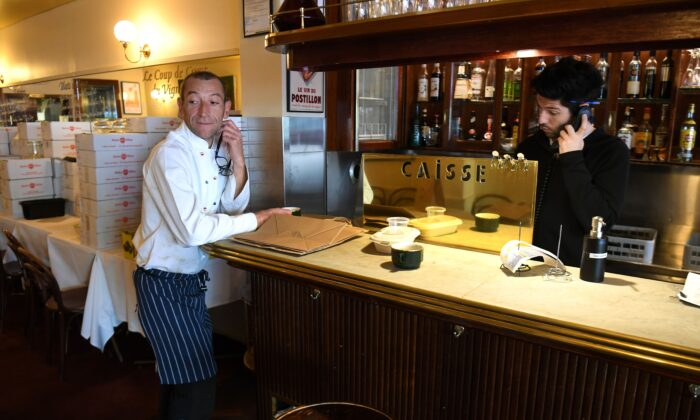 Head chef Geraud Fabre (L) of French restaurant France-Soir waits for take-away orders in Melbourne on May 8, 2020, as Australia's government unveiled a three-stage plan to get economy back.(William West/ Getty Images)