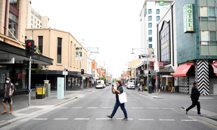 A woman crosses Hindley Street in Adelaide on April 1, 2020 in Adelaide. (Tracey Nearmy/Getty Images)