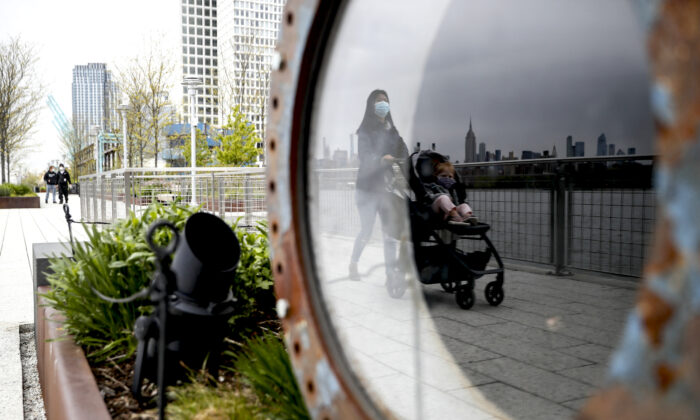 A visitor pushes a stroller while wearing a protective mask at Domino Park, in the Brooklyn borough of New York City, on May 8, 2020. (John Minchillo/AP Photo)