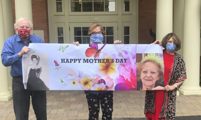 From left, Steve Turner and his sisters, Carla Paull and Lisa Fishman, hold up a Mother's Day banner emblazoned with images of their mom, Beverly Turner, in front of her assisted living facility in Ladue, Mo., on May 3, 2020. (Shelly Solomon via AP)
