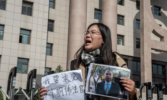 "Xu Yan, wife of human rights lawyer Yu Wensheng, holds a piece of paper the reads ""I want to request a meeting with Judge Liu Mingwei"" and a picture of her husband outside the Xuzhou Intermediate Peoples Court in Xuzhou, China, on Oct. 31, 2019. (Nicolas Asfouri/AFP via Getty Images)"